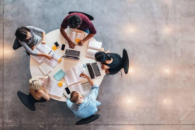 Pessoas trabalhando juntas em mesa: trabalho em equipe