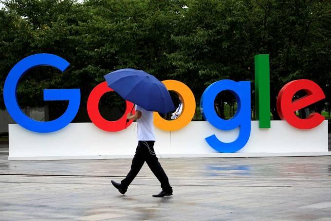 Pessoa caminha em frente ao logo do Google