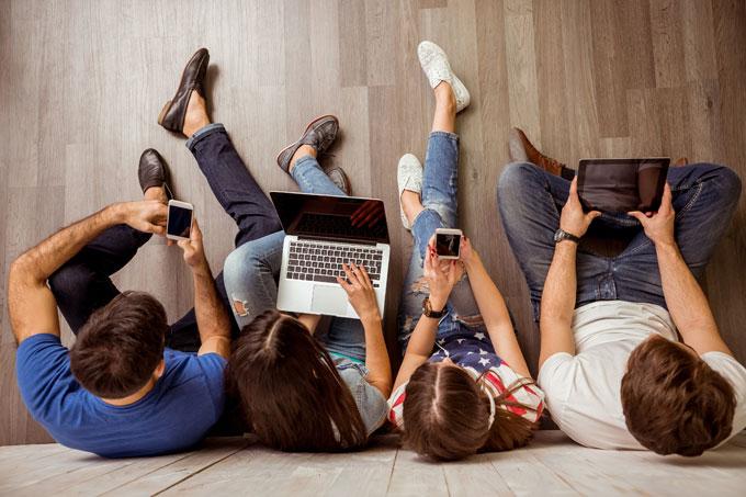 jovens olhando para telas de gadgets e laptops
